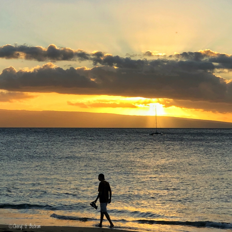 Teen-walks-beach-in-Hawaii-sunset