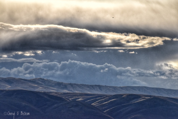Storm clouds layer over sunlit, barren hills