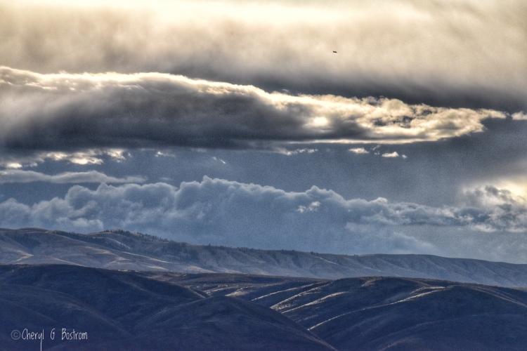 Storm clouds layer over sunlit, barren hills