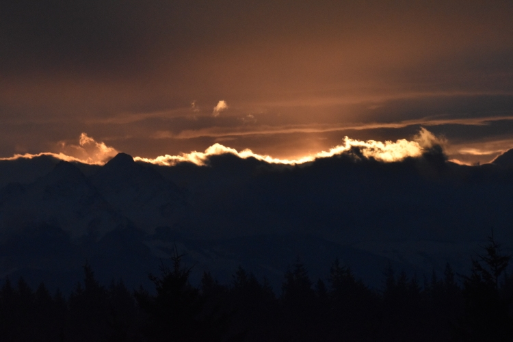 Sunrise turns mountain clouds into a lace trim