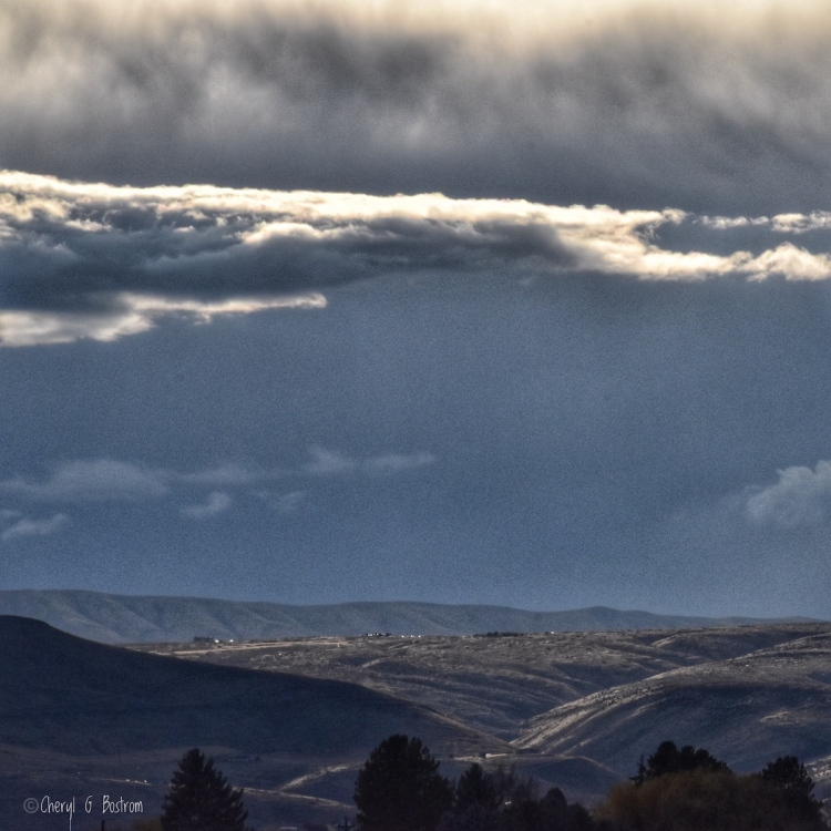 Sunlit storm clouds and hills amidst dark skies over untreed hills