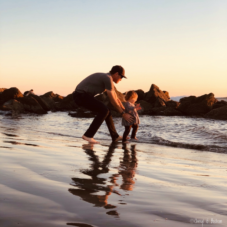 Young dad catches baby daughter as she runs into waves