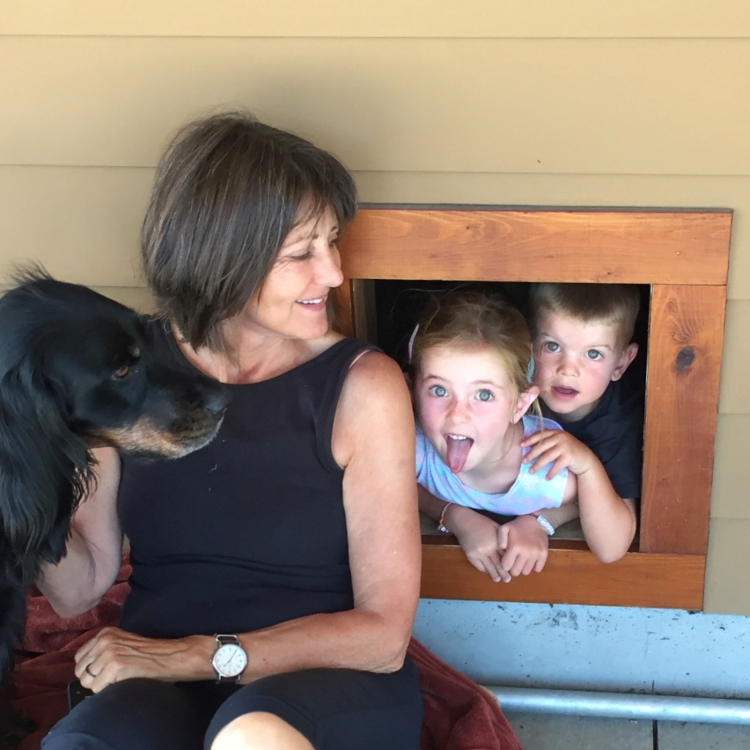 Children peek out of doghouse as Grandma and dog look on